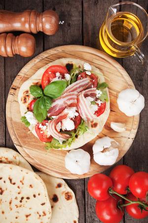comida italiana: Piadina romagnola, s�ndwich de pan plano italiano con ensalada de r�cula, queso ricotta y el tocino de panceta