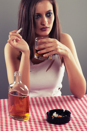 drinking alcohol: Sad woman drinking alcohol and smoking a cigarette
