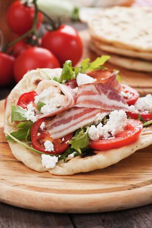 comidas rapidas: Piadina romagnola, s�ndwich de pan plano italiano con ensalada de r�cula, queso ricotta y jam�n Foto de archivo