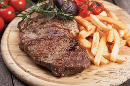 Beef rib-eye steak with french fries on wooden board Standard-Bild