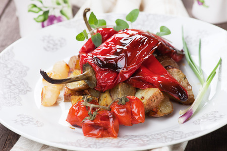 prepared potato: Roasted red peppers with potato and vegetables on white plate Stock Photo