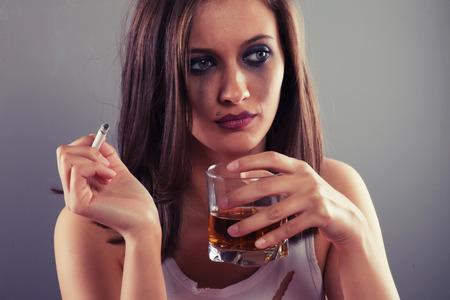 tomando alcohol: Mujer triste beber alcohol y fumar un cigarrillo
