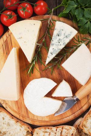 healthy snack: Assorted cheese on wooden platter, rich and healthy snack or breakfast Stock Photo