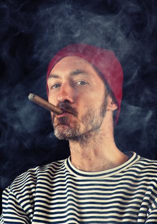 hombre fumando puro: Retrato de hombre marinero fumando un cigarro, dispar� sobre fondo negro Foto de archivo