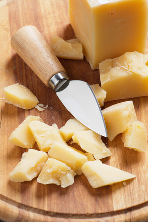 ripened: Hard ripened cheese with knife, on wooden board Stock Photo