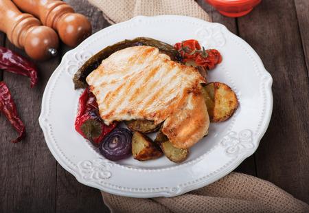 pollo a la brasa: Filete de pollo a la plancha con patata asada y verduras en la mesa de madera