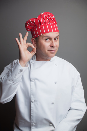 hand sign: Smiling chef with red hat, showing ok hand sign