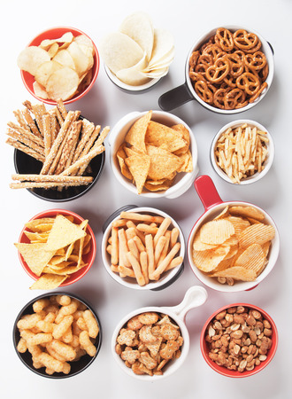sesame cracker: Potato chips,pretzels, roasted peanuts and other salty snacks over white background