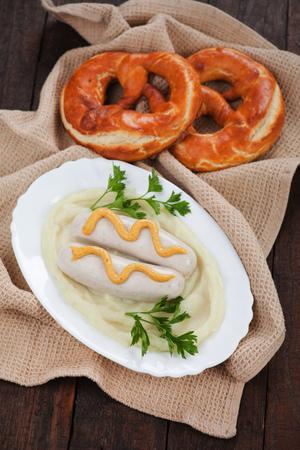 white sausage: German white sausage or wurst served with mashed potato and pretzel Stock Photo
