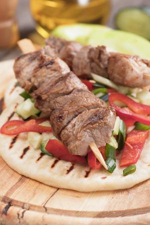 plato de comida: Souvlaki o kebab con ensalada de verduras en pan de pita