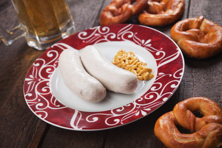 weisswurst: German white sausage or wurst served with mustard and pretzel