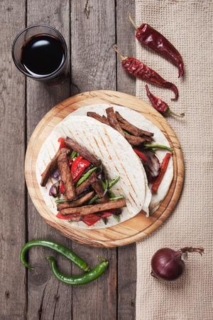 tortilla wrap: Fajitas, mexican beef stripes with vegetables in tortilla wrap