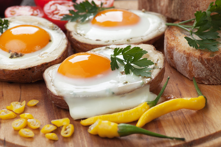 sunny side up: Fried chicken eggs in roasted potato shells served on wooden board Stock Photo