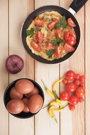 cayenne pepper: Omelet with cherry tomato and cayenne pepper in frying pan