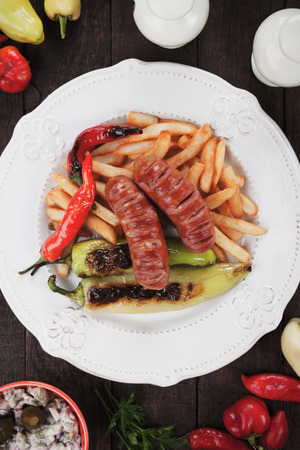 fast meal: Grilled sausages with hot peppers and french fries, popular fast food meal Stock Photo
