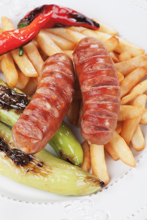 german sausage: Grilled german sausage with french fries and vegetables