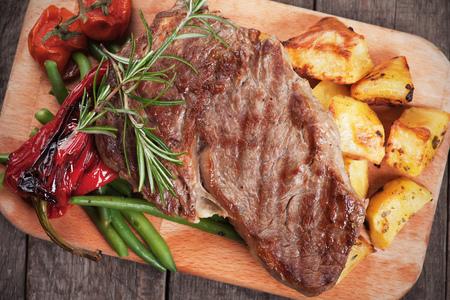 Beef rib-eye steak con patatas y verduras asadas