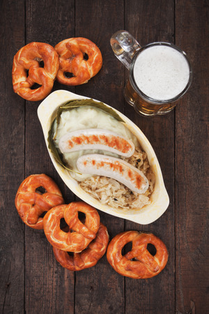 weisswurst: German white sausage or wurst served with sauerkraut and pretzel