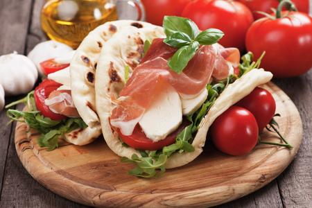 Piadina Romagnola, Italian Flatbread Sandwich with Prosciutto, mozzarella cheese, tomato and rocket salad Stock Photo