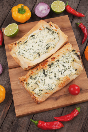 filo pastry: Phyllo pastry filled with cheese and spinach, traditional balkans fast food meal Stock Photo