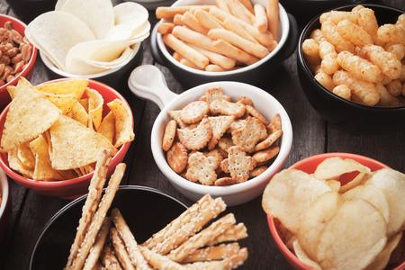 botanas: galletas saladas, chips de tortilla y otros aperitivos salados con la inmersión de la salsa Foto de archivo