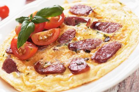 saucisse: Omelette à la saucisse pepperoni, tomate cerise et basilic servi sur un plateau