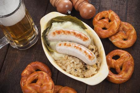 comida alemana: salchicha blanca alemán o salchicha servido con chucrut y pretzel