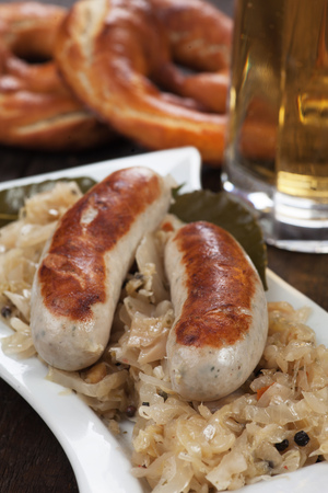 weisswurst: Grilled german white sausage with suaerkraut or sour cabbage and pretzel