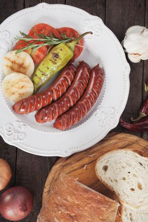 german sausage: Grilled german sausage and vegetables on wooden table