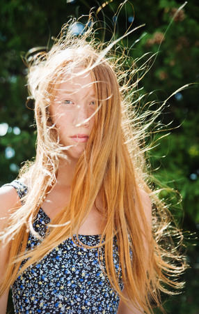 red haired girl: Portrait of young red haired girl on a windy summer day Stock Photo