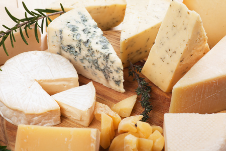 cheese plate: Assorted cheese on wooden platter, rich and healthy breakfast or snack food