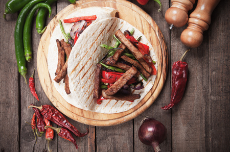 burrito: Fajitas, mexican beef stripes with vegetables in tortilla wrap