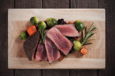 brussel: Medium rare beef steak with carrot and brussel sprout on wooden board