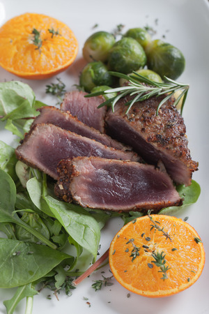 venison: Rare beef or venison steak with herbs, lettuce and brussel sprout Stock Photo