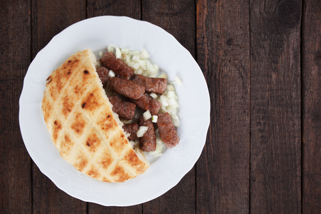 Cevapsici, bosnian minced meat kebab with diced onion and somun bread