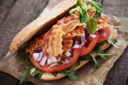 fried foods: Sandwich with fried bacon, tomato and onion