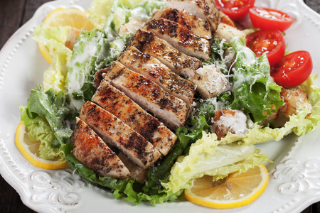 CHICKEN CAESAR SALAD: Grilled chicken steak served over caesar salad