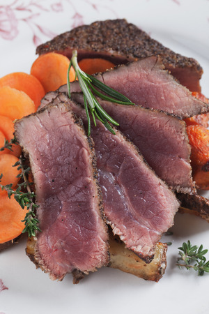 the medium: Medium rare beef pepper steak with carrot, thyme and rosemary