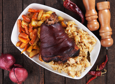 Roasted pork knuckle with baked potato, carrot and sour cabbage Stock Photo