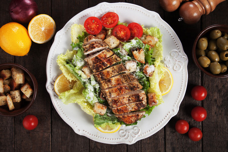 Grilled chicken steak served over caesar salad