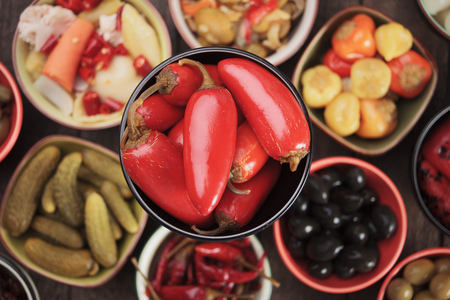 pickled: Pickled red jalapeno chili peppers with other pickles as background