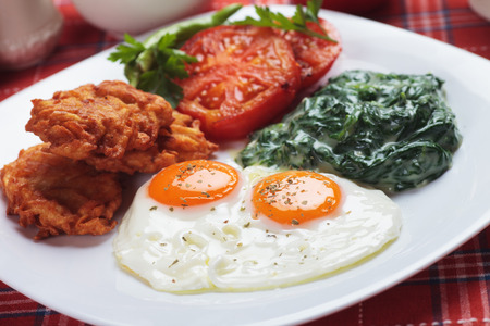 chicken and egg: Fried eggs served fot preakfast with spinach, tomato and potato pancakes