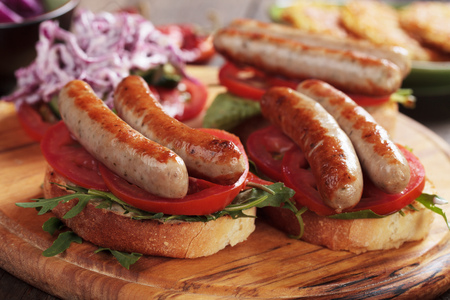 Grilled sausage sandwich with tomato and rocket salad