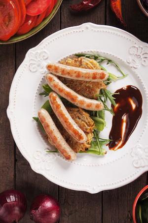 papas doradas: Salchichas a la parrilla servido sobre croquetas de patata con ensalada de rúcula y salsa de barbacoa