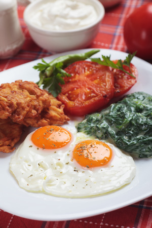 chicken and egg: Fried eggs served for breakfast with spinach, tomato and potato pancakes Stock Photo