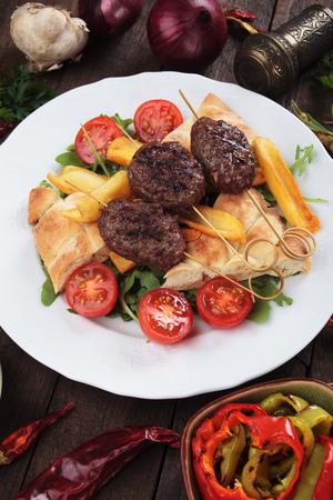 Turkish kofta kebab, minced meat skewer with fried potatoes and flatbread Stock Photo