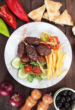 carne asada: kebab turco kofta, pincho de carne picada con ensalada y patatas fritas