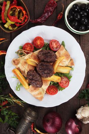 carne asada: Kofta kebab, oriental pincho de carne picada con pan de pita y patatas fritas Foto de archivo