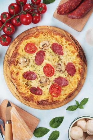 Italian spaghetti pizza with salami pepperoni and mushrooms
