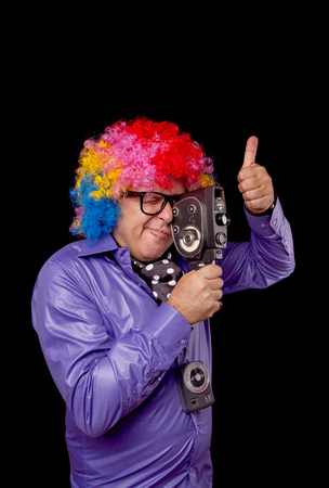 old photograph: Man with rainbow afro wig recording a movie with retro film camera